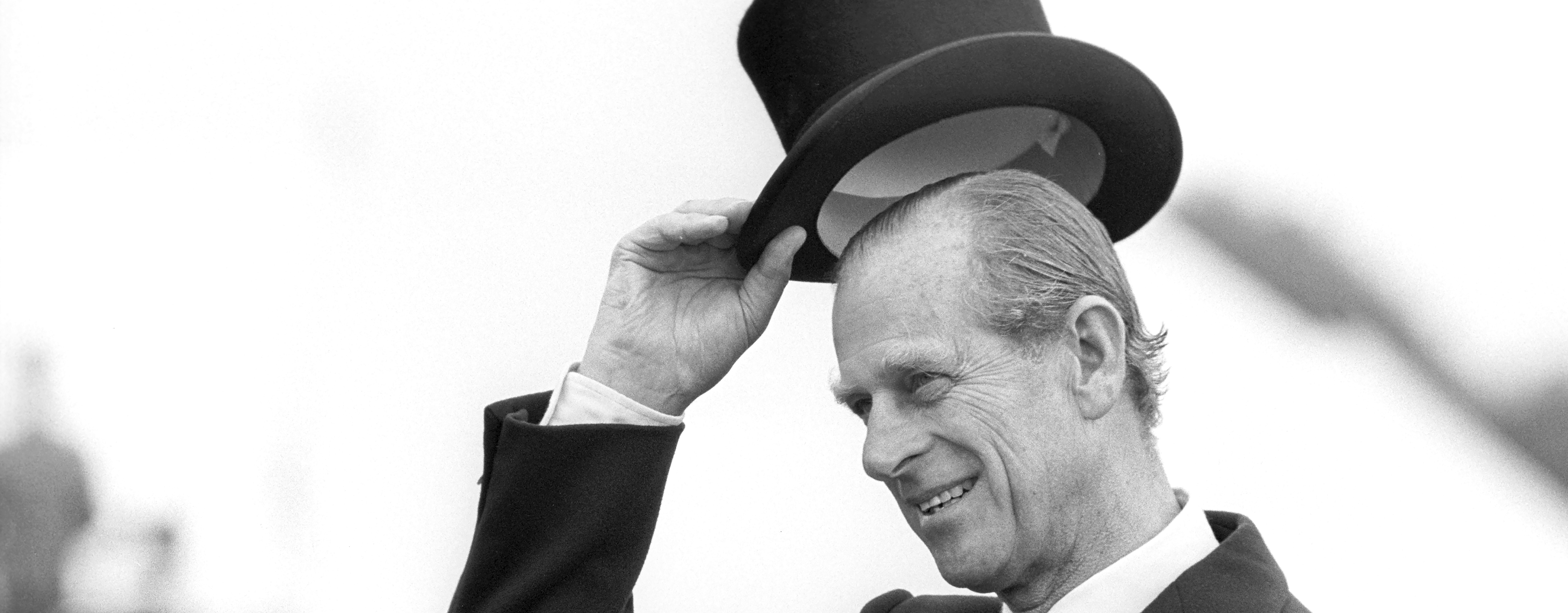 Prince Philip raises his top hat to acknowledge a crowd