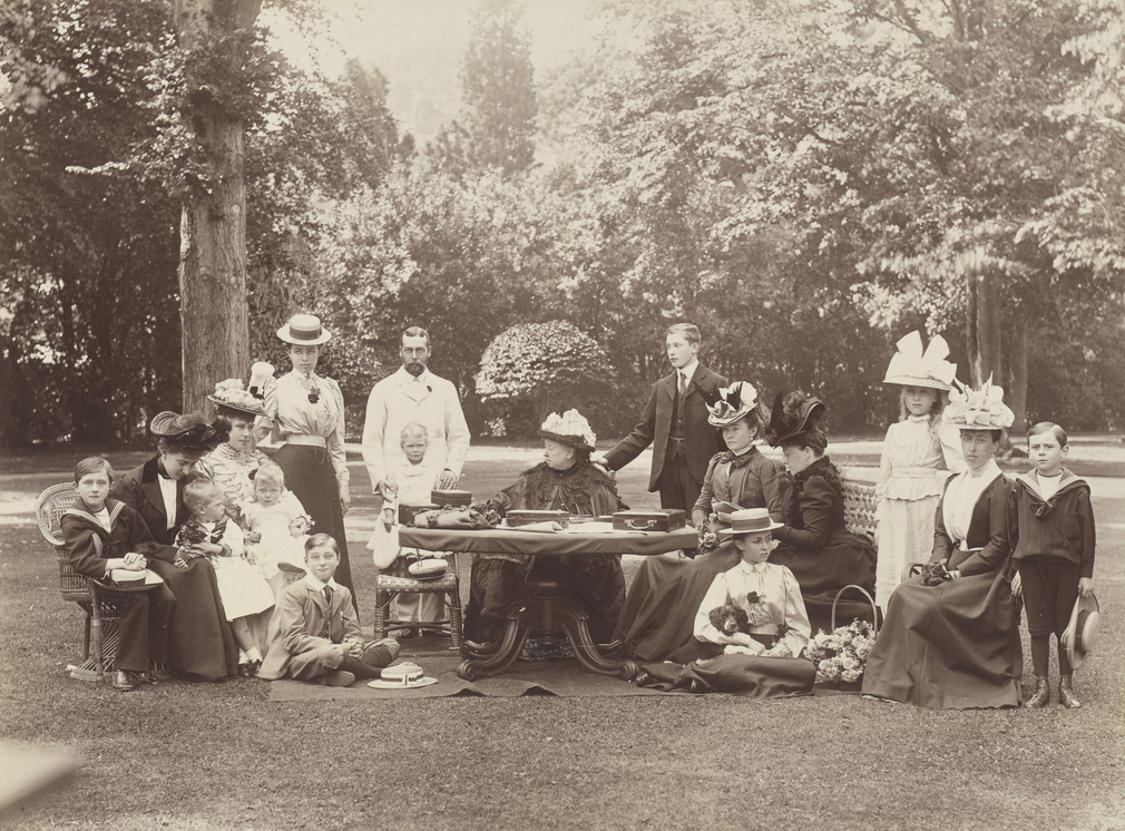 A group photograph taken at Osboune House, including Queen Victoria (1819-1901); Queen Mary (1867-1953) when Princess Mary, Duchess of York, holding Mary, Princess Royal and Countess of Harewood (1897-1965), when Princess Mary of York, on the Duchess's la