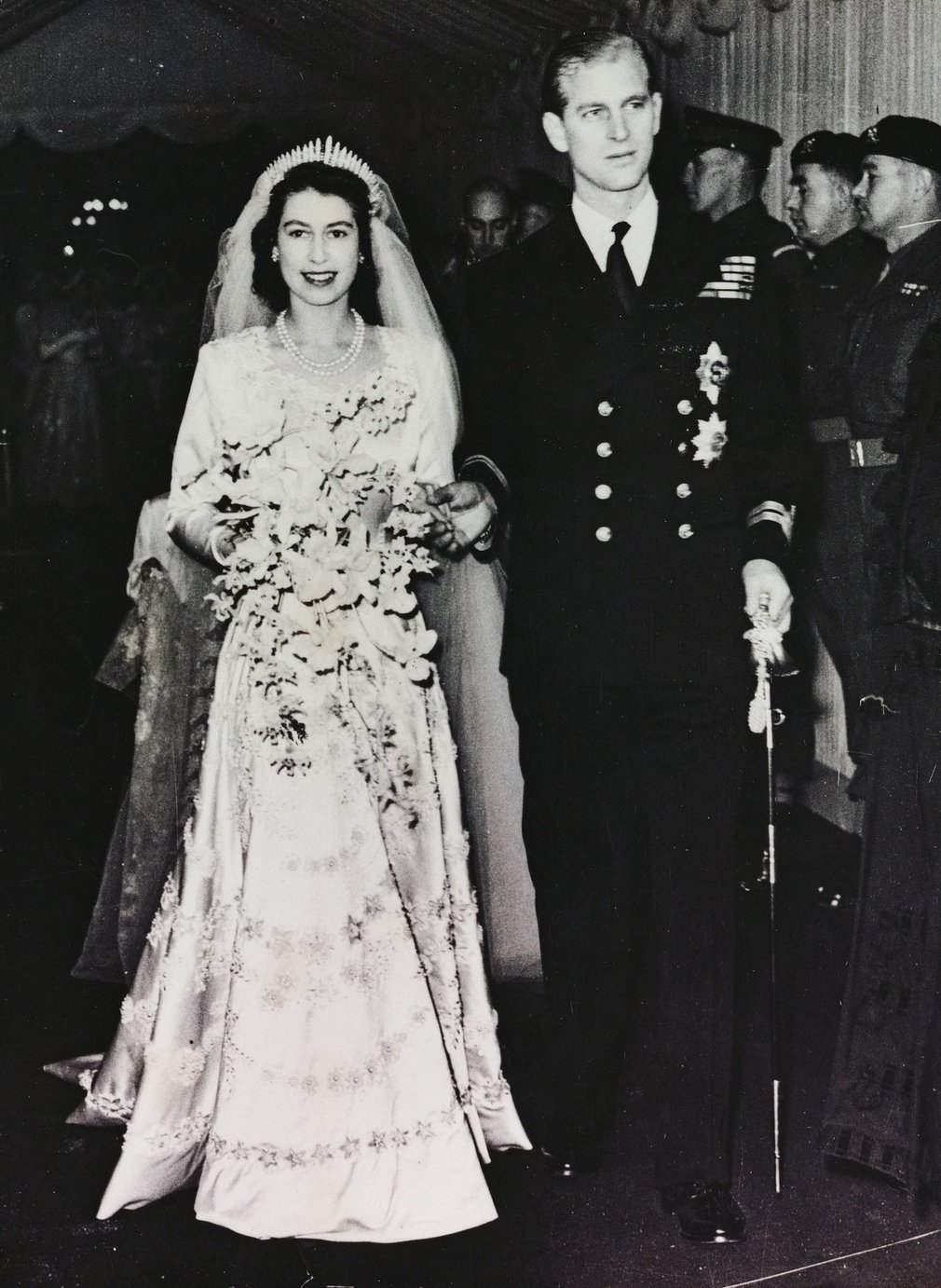 Photograph of HM Queen Elizabeth II (b.1926), when Princess Elizabeth, and HRH The Duke of Edinburgh (b.1921) leaving Westminster Abbey on their wedding day.The wedding dress was designed by Norman Hartnell and was embroidered with hundreds