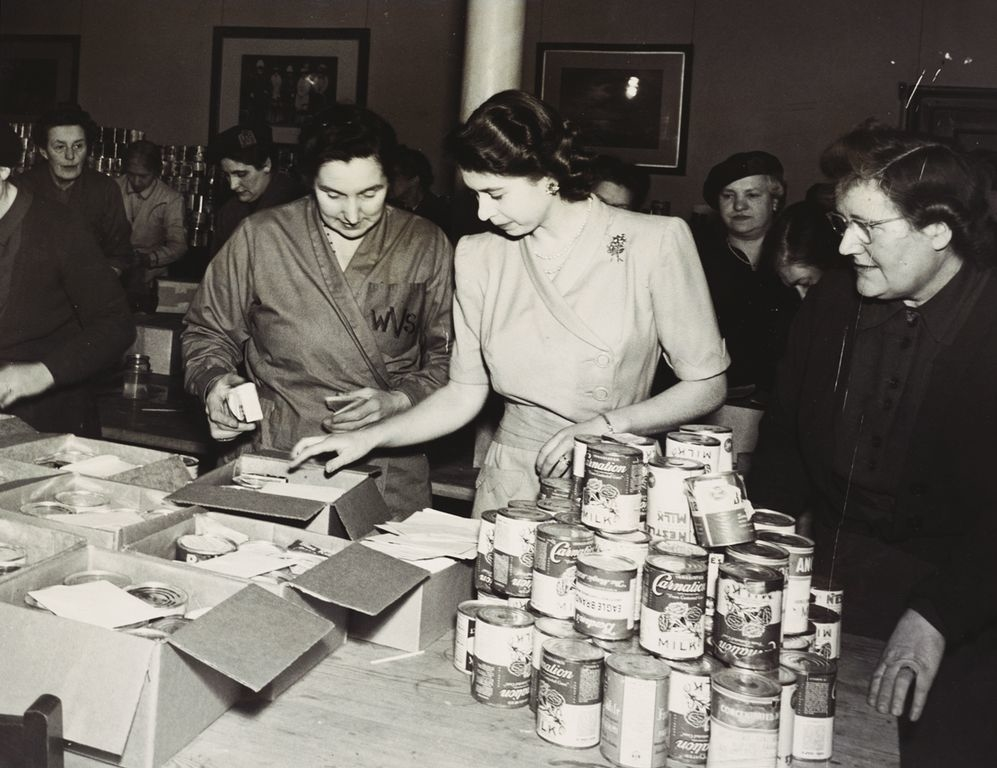 Photograph of HM Queen Elizabeth II when Princess, at Buckingham Palace, supervising the packing of food parcels by the Women's Voluntary Services for pensioners and widows. The food was sent by the Dominions and Colonies as a wedding present for Princess
