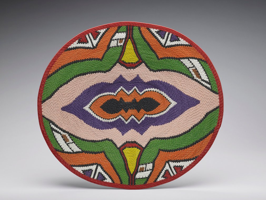A colourful shallow basket made of telephone wire (an imbenge).  Traditional Zulu baskets were tightly woven from grasses and palm leaf. Today, craftspeople living in urban areas recreate many of the old patterns and forms with a new medium- recycl