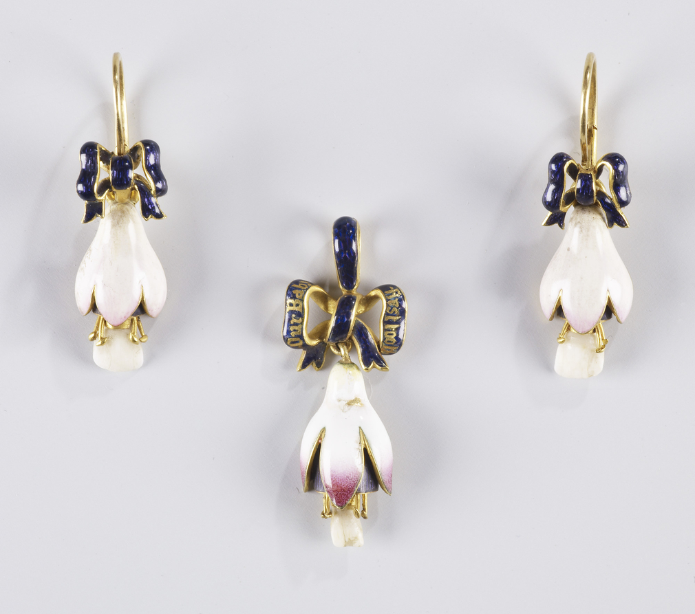 A pendant and a pair of gold mounted enamel earrings in the form of a fuscia flower set with milk teeth from Princess Beatrice (1857-1944), Queen Victoria's youngest child. These are suspended from an enamelled ribbon.<br /><br />The work of setting the t