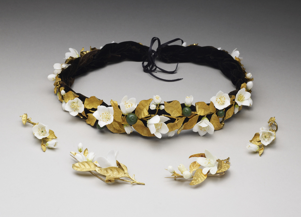 Headdress in the form of a wreath of orange blossoms with gold leaves, white porcelain flowers and green enamelled oranges. Black plaited velvet band, and silk ribbon. Within the language of flowers, one remarkably consistent usage was the symbolic meani