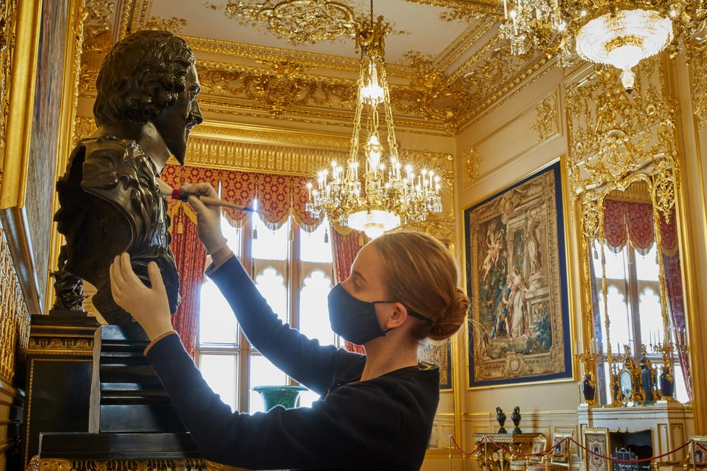 A member of staff dusts a bronze bust of Charles I in the Grand Reception Room at Windsor Castle