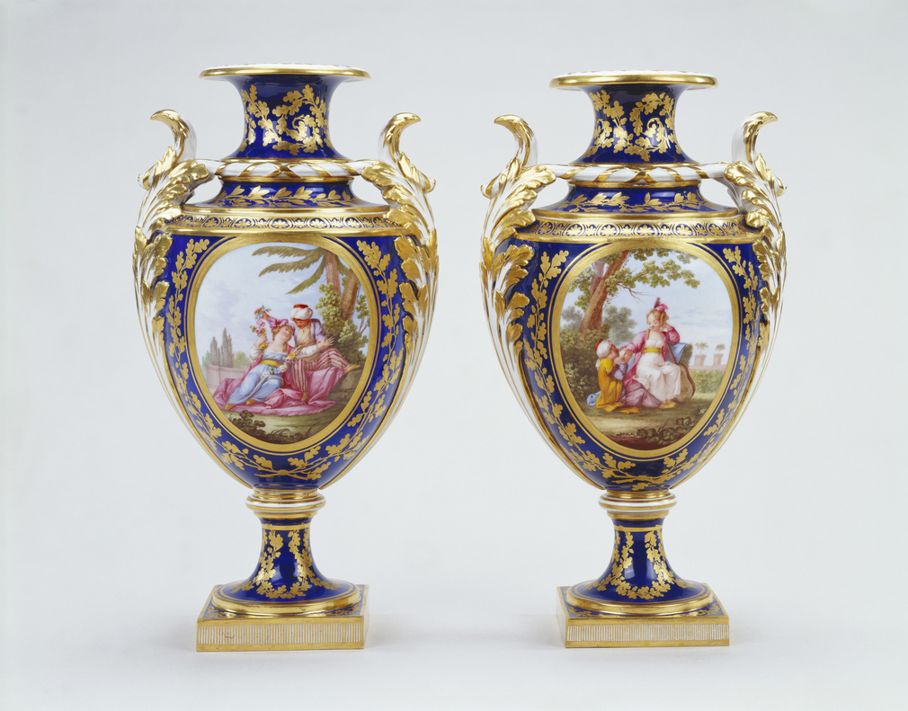 Sèvres soft paste porcelain, pair of vases.  Bleu nouveau ground with gilded decoration. Oval shape, trumpet shaped mouth and acanthus shaped handles; circular stem and foot with square base. Reserves painted with Turkish figures in garden landscape, rev