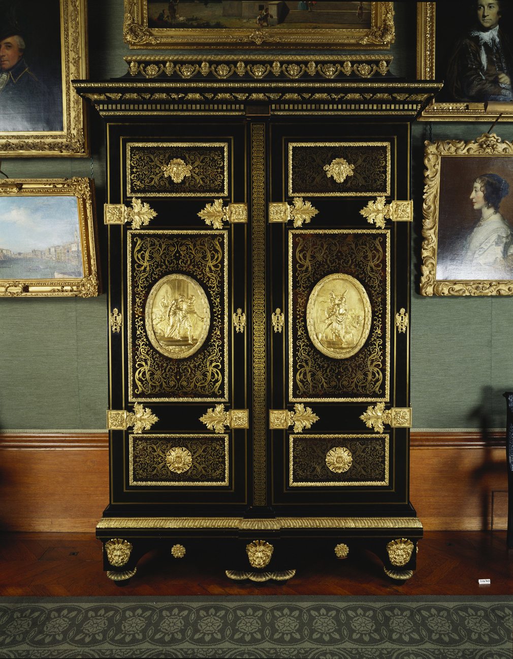 Tall rectangular armoire, inlaid with tortoiseshell and brass boullework, with gilt bronze mounts. Two panelled doors, each in three sections; the upper sections centred with gilt bronze masks, the lower sections with gilt bronze rosettes and the central