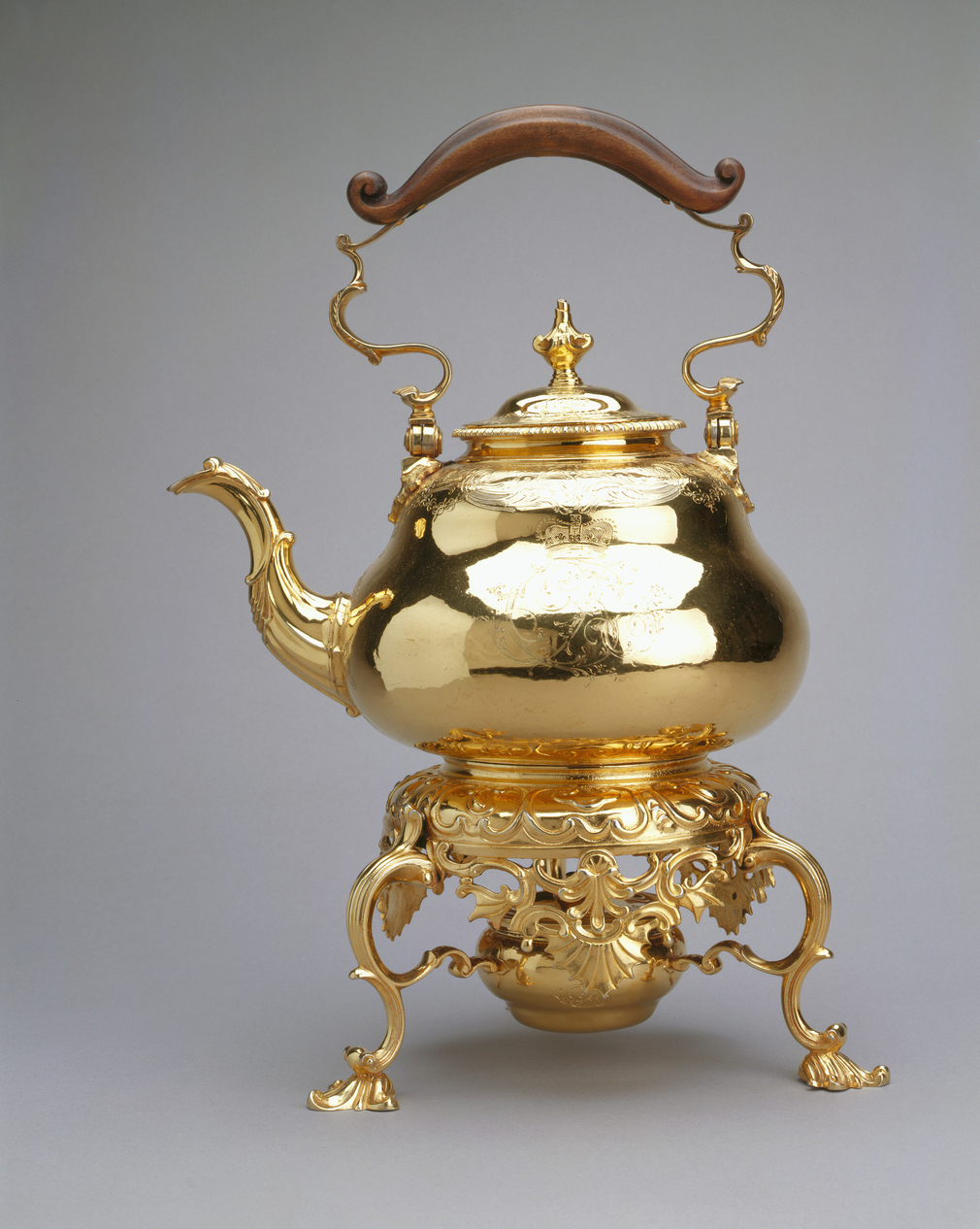 Silver gilt tea kettle. Hinged bail handle with ebonised wooden grip. Domed detachable cover with baluster finial. Pear shaped kettle with curved spout; engraved with foliate scrolls and crowned CR monogram. Circular stand with pierced apron; on 3 scroll