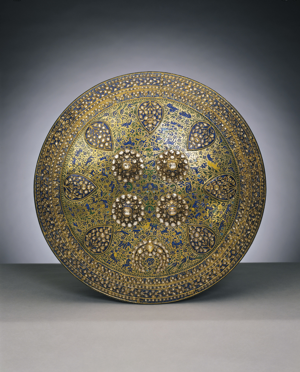 Like the weapons and other articles presented to Albert Edward Prince of Wales during his four-month tour of India in 1875-76, this is a particularly elaborate and rich example of a traditional form. Shields of this type, or dhal, were usually made of hid