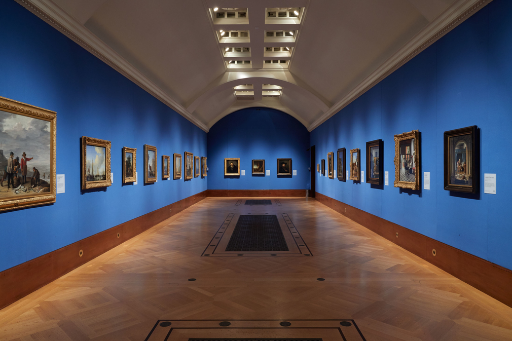 Blue walls with paintings hanging, polished wood floors with metal grills.