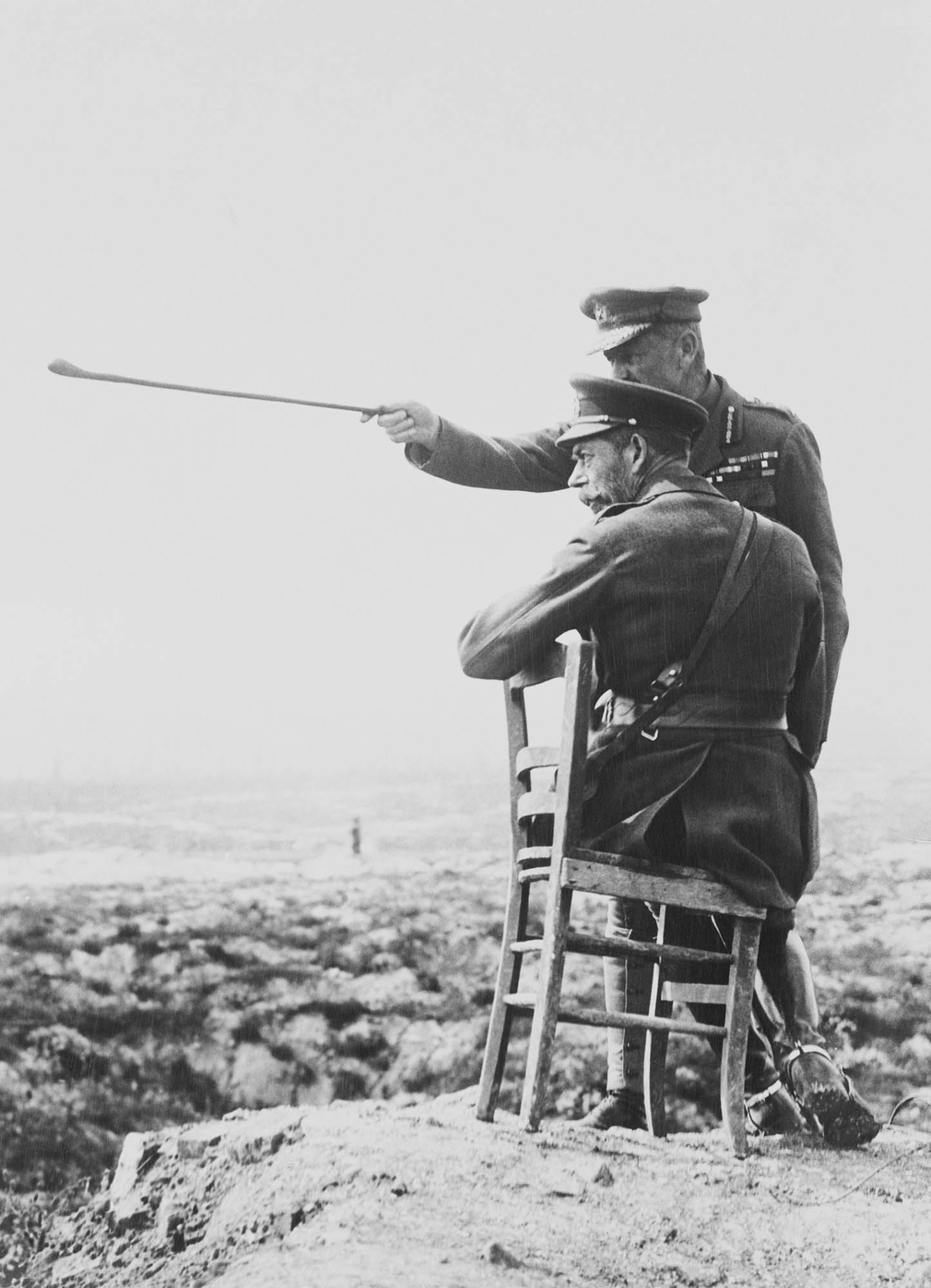 Photograph showing King George V (1865-1936) sitting on a chair on top of a spoil heap, talking with an unidentified gentleman wearing military uniform who is pointing his stick out, which the King is looking towards in the distance. There is a derelict l