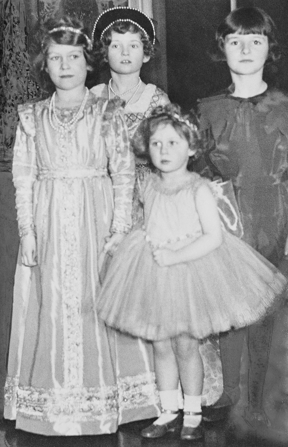 Photograph of Princess Elizabeth of York (1926- ) and Princess Margaret of York (1930-2002) attending a fancy dress party. The Princesses are photographed with two other unidentified girls.