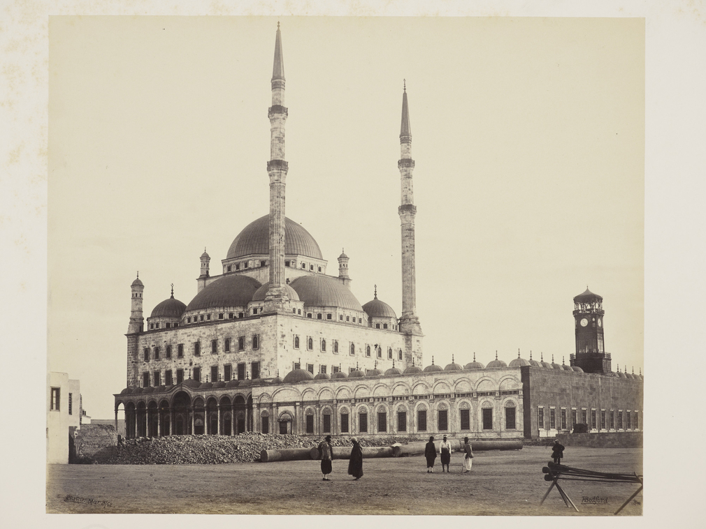 View of Mosque of Mohammed Ali in Cairo, Egypt. Alabaster building seen across square, with 2 tall minarets centre. Single row of columns supporting round arches lining court, left.  The mosque was built in the Ottoman style between 1830 and 1848 for th