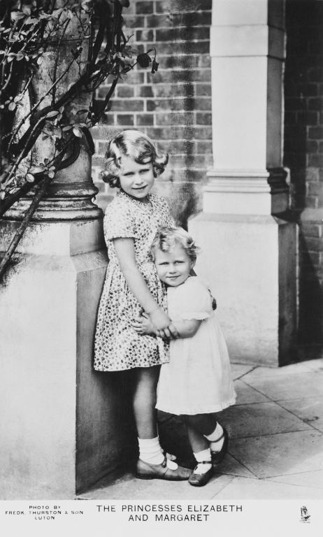 Double portrait post card photograph of HM Queen Elizabeth II (1926- ) when Princess Elizabeth of York and Princess Margaret (1930-2002) when Princess Margaret of York, standing together next to a pillar outside an unknown property
