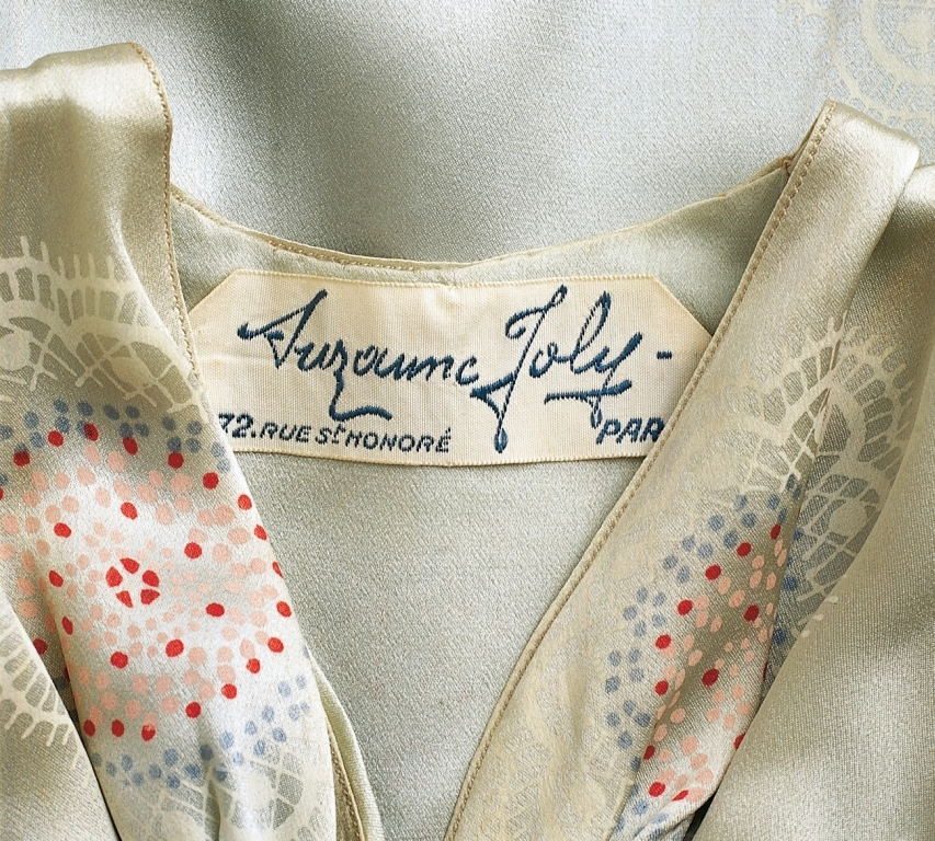 A pair of satin evening dresses with fish tails, puffed sleeves, gathered bodice with long blue velvet ties at waist. One white, printed with pink, blue and white flowers. The other blue, printed with pink blue and white flowers.