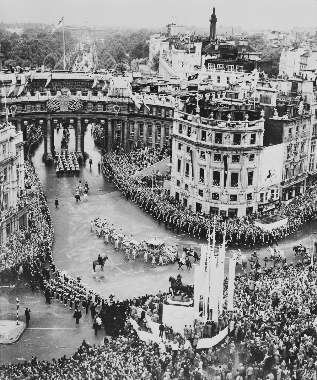 Photograph shows the Gold State Coach carrying The Queen as it passes through Trafalgar Square enroute to Buckingham Palace after the Coronation Ceremony in Westminster Abbey, pass cheering crowds