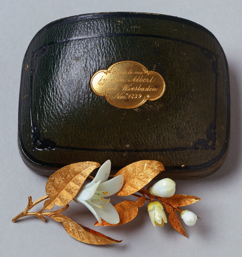 Pair of brooches in the form of a sprig of orange blossom with gold leaves and white porcelain flowers; one in a green leather box mounted with plaque, engraved with inscription: Sent to me/ by dear Albert/ from Wiesbaden/ Novr. 1839.    Within the langua