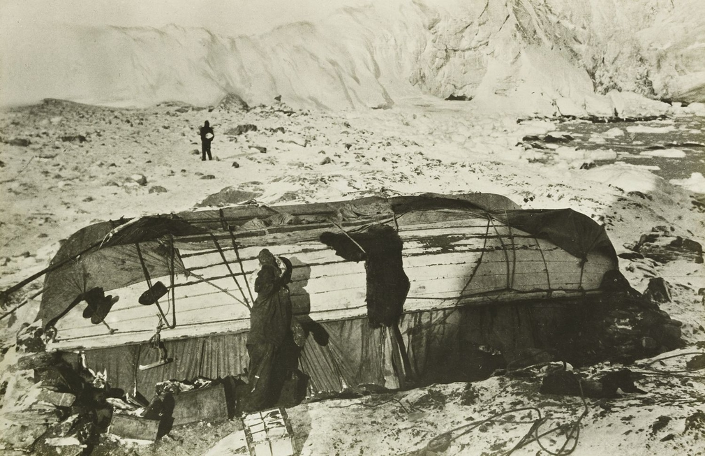 Photograph showing the 'Dudley Docker' and the 'Stancomb Wills' upside down and fringed with remains of tents. A man is visible in the distance.  After attempts to dig ice caves, the men built a hut from the 'Dudley Docker' and the 'Stancomb Wills' - tw