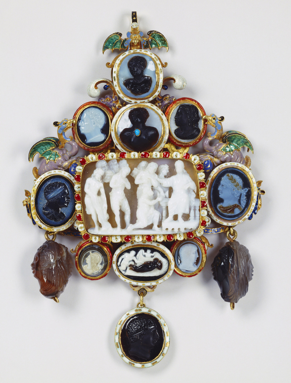 Gold openwork pendant with opaque white and middle-blue enamel foliate scrolls and two dragons on cornucopiae in opaque mauve, translucent green and opaque pale-blue émail en ronde bosse on either side of a central arched niche. The jewel is surmou