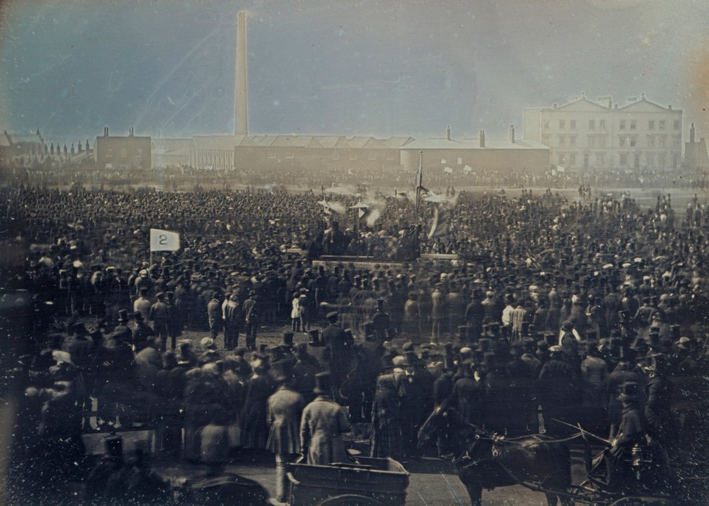 Daguerreotype of a large crowd of supporters of the Chartist movement gathered together on Kennington Common. At the centre of the crowd there is a platform for the speakers, and a number of people hold banners and flags. Behind the crowd there is a tall