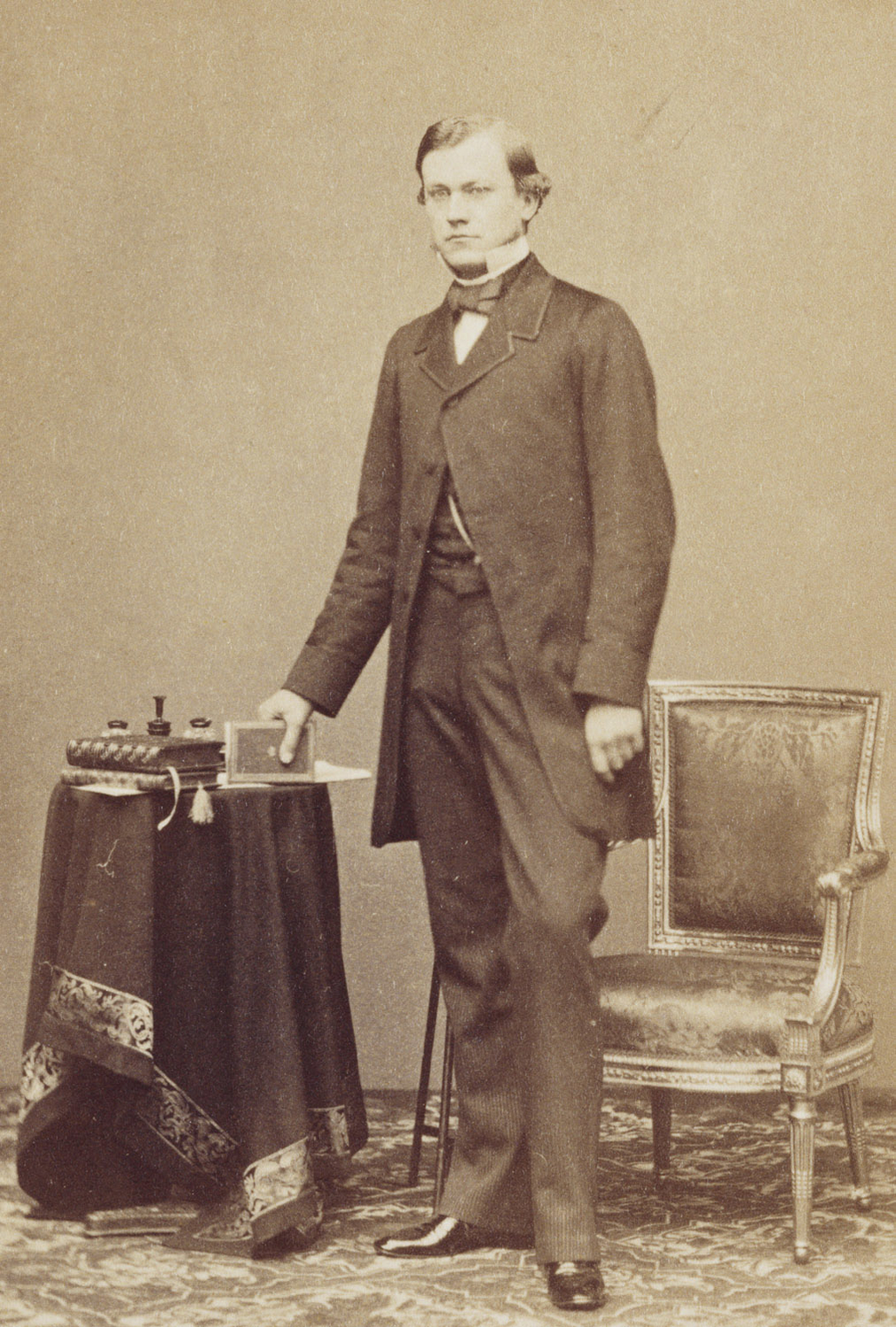 Photograph of CarlRuland, standing beside a chair, holding a book in his right hand, looking at the camera. He was an art and literary historian; Private secretary to Prince Albert and assisted with the Raphael Project.