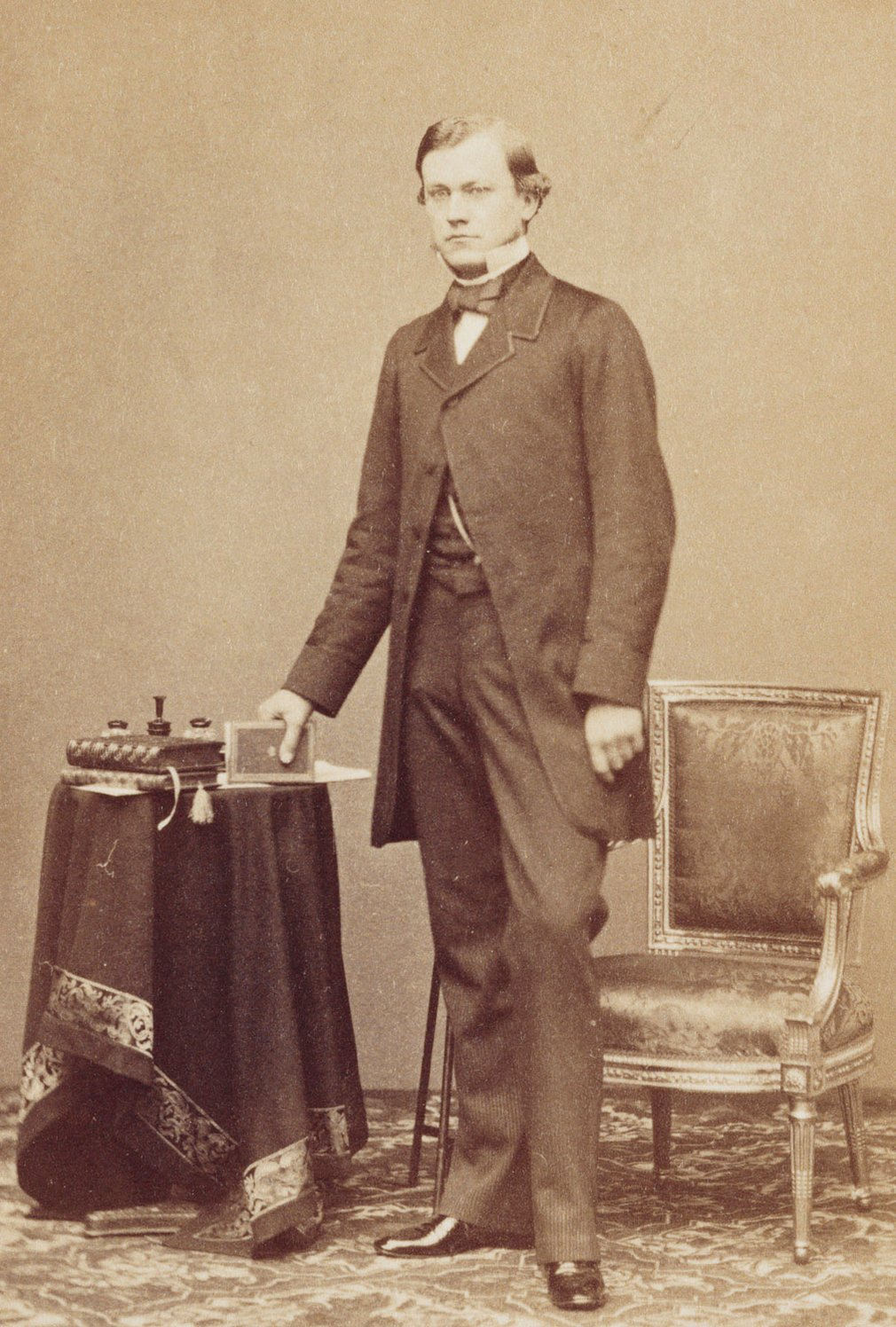 Photograph of Carl Ruland, standing beside a chair, holding a book in his right hand, looking at the camera. He was an art and literary historian; Private secretary to Prince Albert and assisted with the Raphael Project.