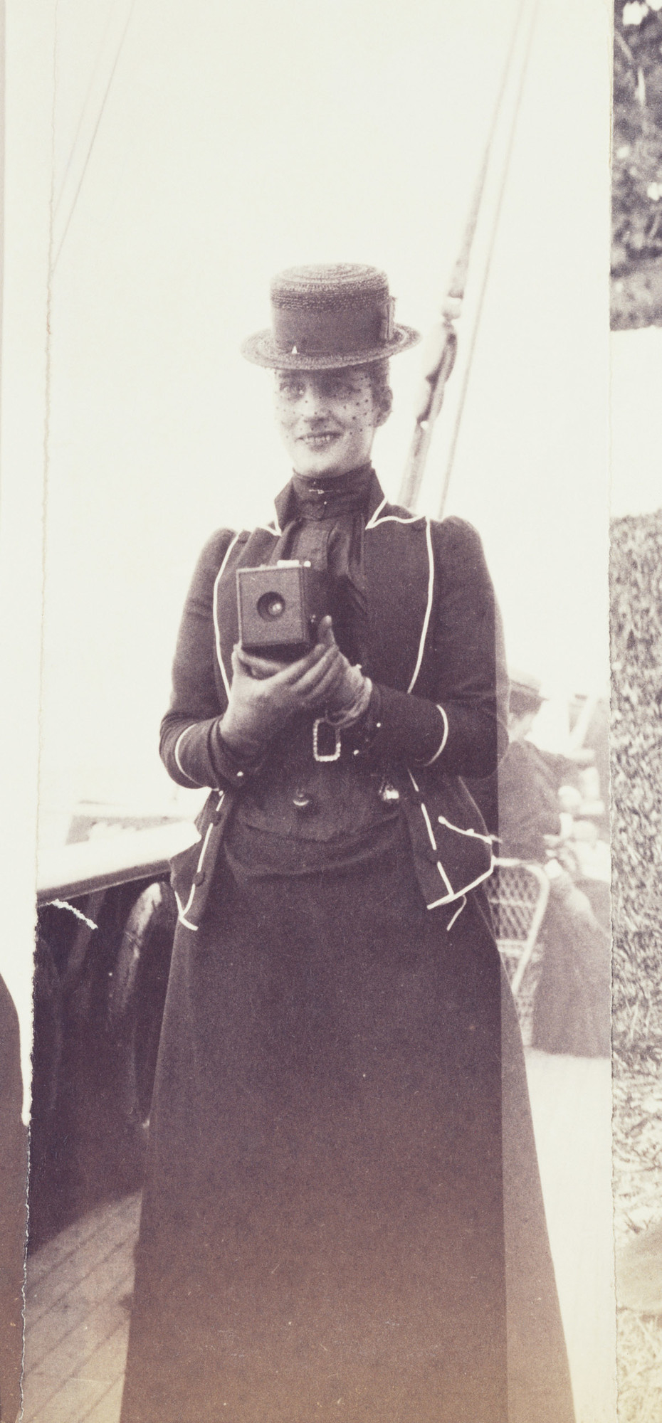 Photograph of the Princess of Wales, later Queen Alexandra, holding a No.1 Kodak camera at chest height. She is standing on the deck of a ship. The No.1 Kodak camera was introduced in 1889 andtook small circular photographs. There are many exa