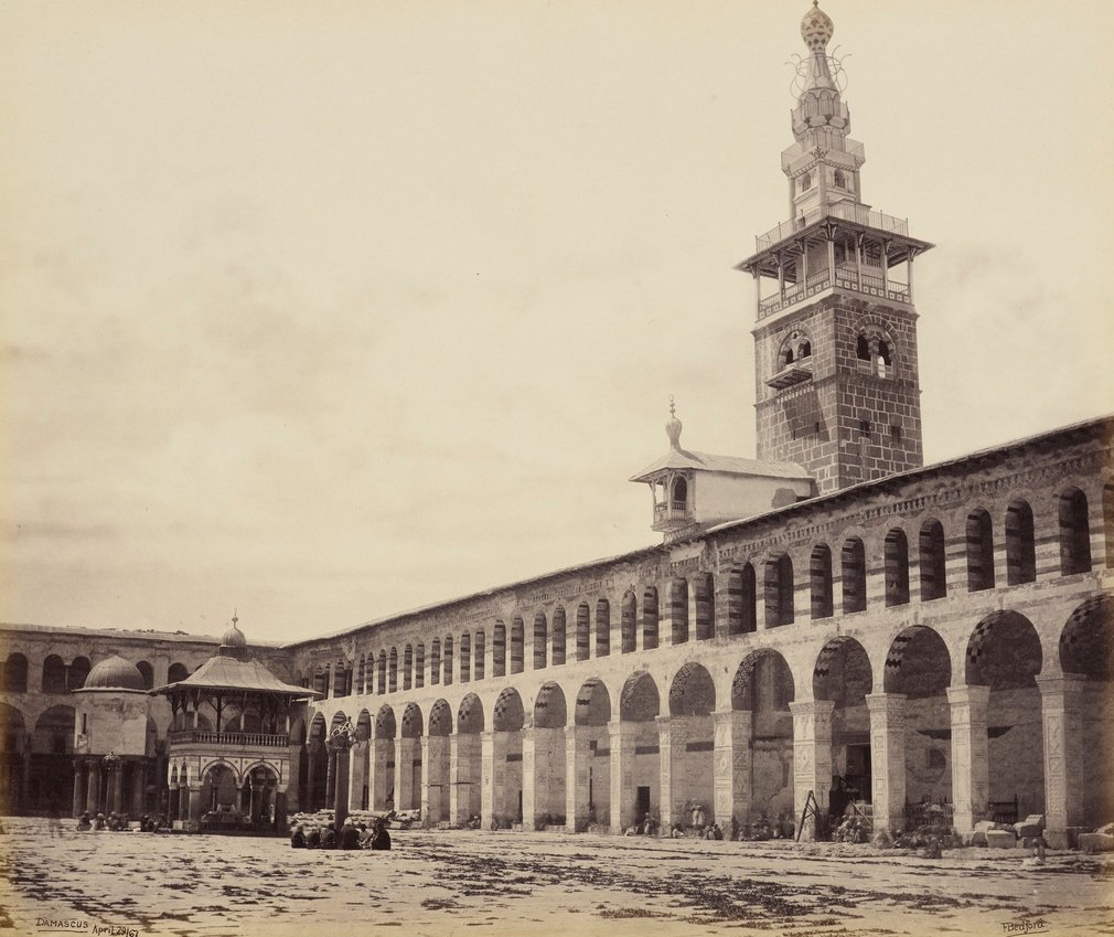View across the court of the mosque from the north side. Colonnade runs the length of the interior, tower above. Fountain covered by pavilion to the left.