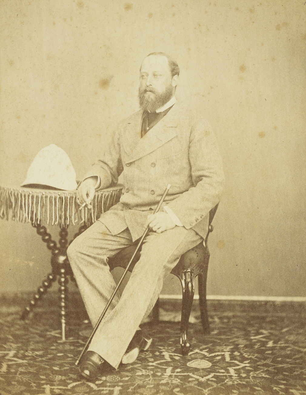 Photograph showing full length portrait of Albert Edward, Prince of Wales, seated, holding a cane in his left hand and a cigarette in his right, leaning on a small, three-legged table on which is a pith helmet. The Prince of Wales visited Jaipur in early