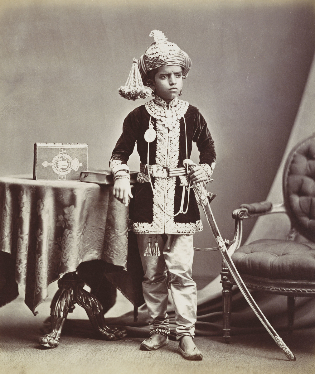 Photograph of Sayaji Rao III Gaekwar, Maharaja of Baroda, who stands facing front, head turned slightly right. He leans with his right arm on book on top of circular table, which also has a second, upright book with the Prince of Wales motif. He wears tur