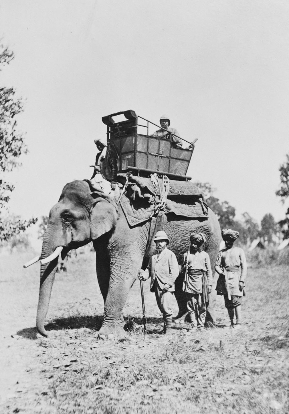 Photograph of elephant, standing with a driver and passenger on board. The Prince of Wales, later King Edward VII (1841-1910) and two Indians are standing in front of the elephant.