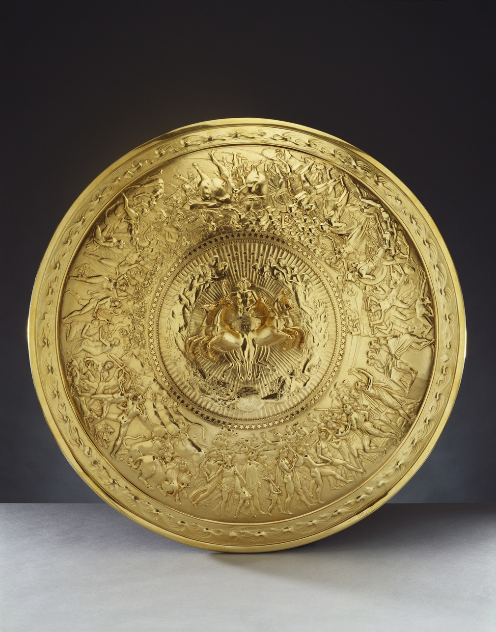 A silver-gilt convex shield with a central medallion cast in high relief with Apollo in a quadriga, surrounded by stars and female figures representing the constellations. The broad border is cast in low relief with scenes of human life (a wedding and ban