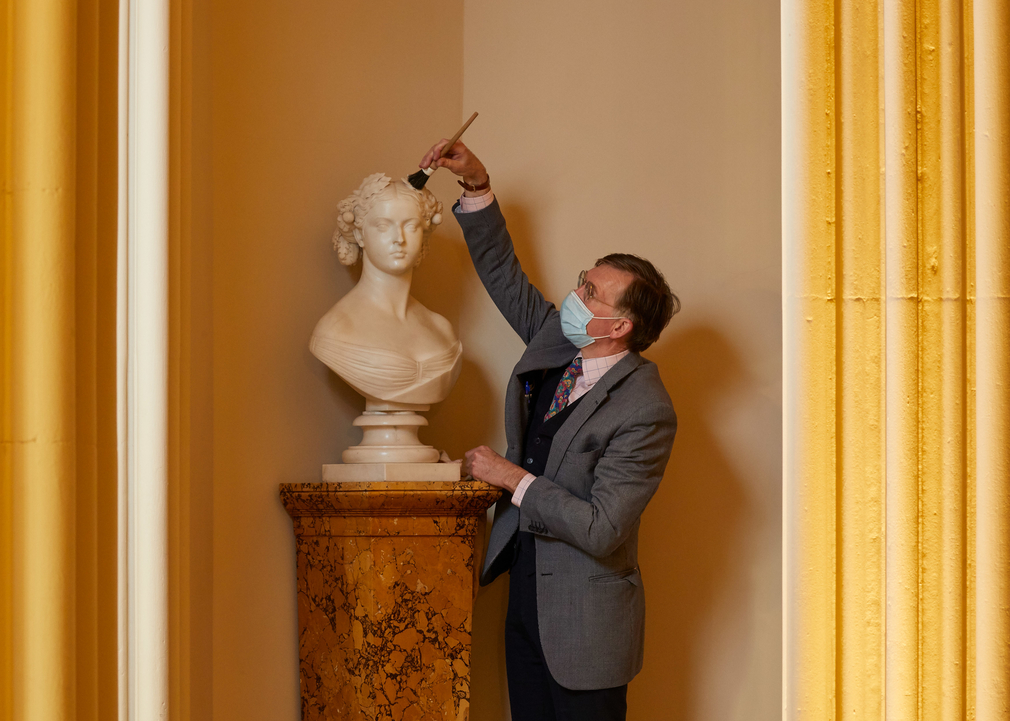 A member of staff carefully cleans a newly installed marble bust of Queen Victoria in Windsor Castle's Inner Hall