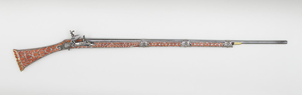 Miquelet lock gun. Lock and stock Algerian, barrel French c.1780Iron, silver and gilt, hardwood, coral. Lock inscribed in Arabic made by 'AMAL MAHMUD, dated 1206 A.H (1791 A.D)Barrel stamped Merley Carteron, and Crown B?, and originally blued.Silver stamp
