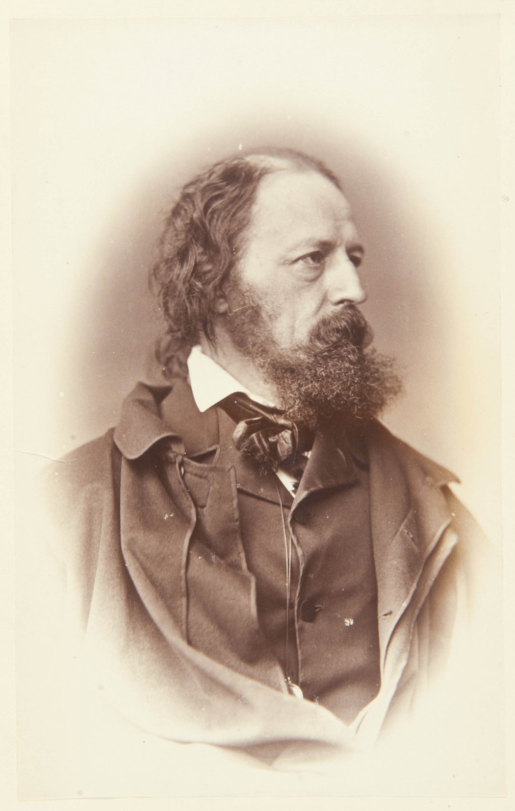 Photograph of the poet Alfred Tennyson facing three-quarters right. He wears an overcoat or cloak over a jacket with high lapels. He wears a pince-nez or eyeglass attached to a string around his neck. Half-length portrait.