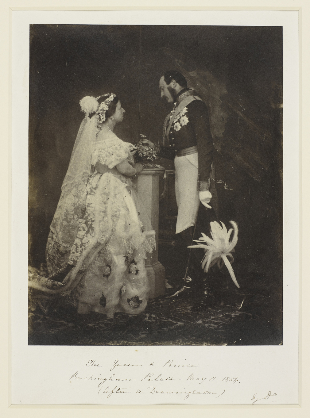 Photograph showing a full length portrait of Queen Victoria (1819-1901) and Prince Albert (1819-61). Queen Victoria stands in right side profile and wears formal court dress. Prince Albert stands in left side profile, holding a feathered hat in his left h
