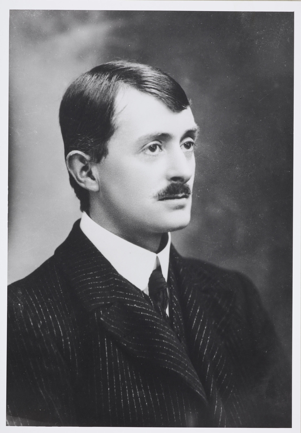 Photograph of a head and shoulders length portrait of the Poet Laureate and holder of the Order of Merit, John Masefield. He faces three-quarters right and wears a dark jacket, white shirt and tie.