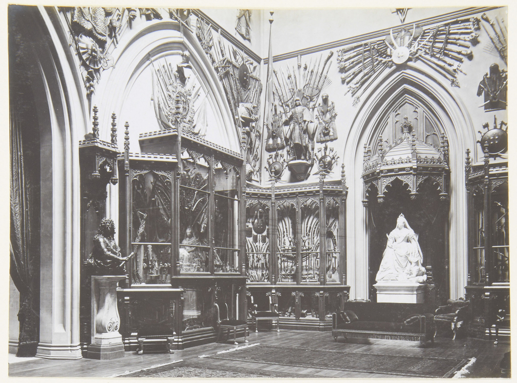 Photograph of the Grand Vestibule, with Boehm's statue of Queen Victoria with a collie (RCIN 35336) under a wooden Gothic canopy. The walls are lined with Gothic display cabinets filled with mostly weapons; above them are displays of a