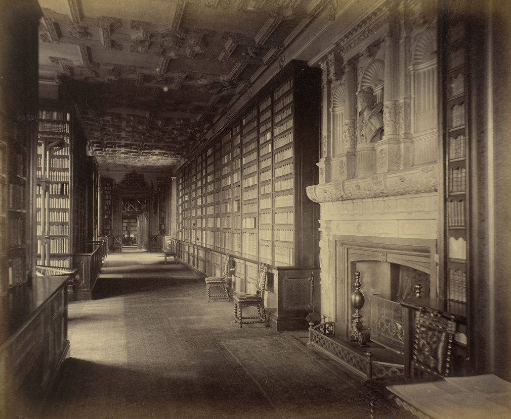 Queen Elizabeth's Gallery, in the Royal Library, WC. Shelves filled with books are either side of the walkway, chairs stand to the right. Window bays are on the left & a fireplace with carved niches and a bust above are (near) right.
