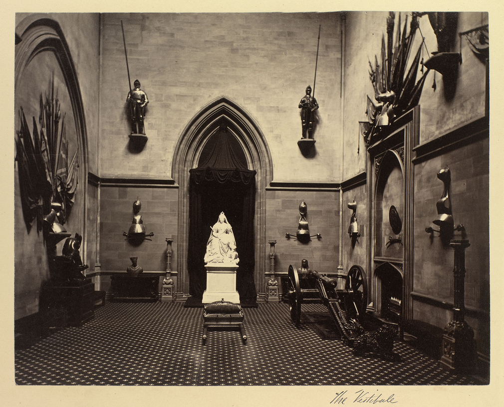 The Grand Vestibule, Windsor Castle. Suits and pieces of armour are mounted on the walls and a cannon stands on the floor. In front of the arch on the rear wall is Sir Edgar Boehm's statue (1871) of Queen Victoria.
