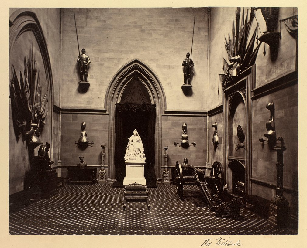The Grand Vestibule, Windsor Castle. Suits and pieces of armour are mounted on the walls and a cannon and an animal sculpture is on the floor to right. In front of the arch on the rear wall is Sir Edgar Boehm's statue of Queen Victoria (RCIN 35336). On ei