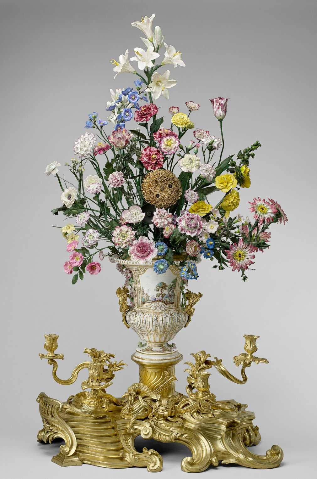 A gilt bronze clock in the form of a sunflower, mounted into the centre of a Vincennes porcelain urn shape vase containing a bouquet of flowers, also of Vincennes porcelain, on stems of green laquered brass wire. Arranged as a loose bouquet, the porcelai