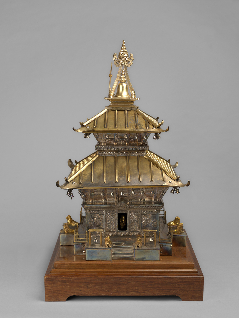 A model of a silver temple of Pashupati Nath in gilt-metal fixed to a square wooded stand. Two pagoda-style roofs with suspended bells, a pair of lions at each of the four doorways. Walls embossed with Eastern patterns.