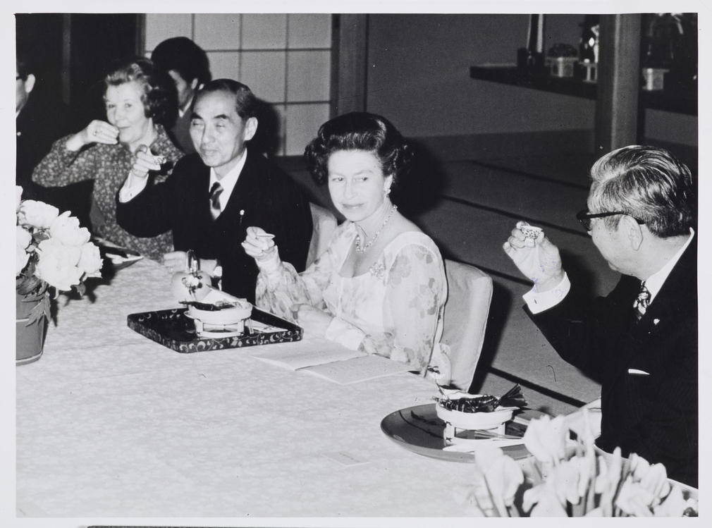 In the centre of picture, the Queen sits Japanese style on a tatami floor mat whilst drinking Saki in a restaurant. Far left sits Lady Shepherd and Mr Nakagawa (Head of Suite of Honour). On Queen's left sits Mr Yukawia,Master of Ceremonies.