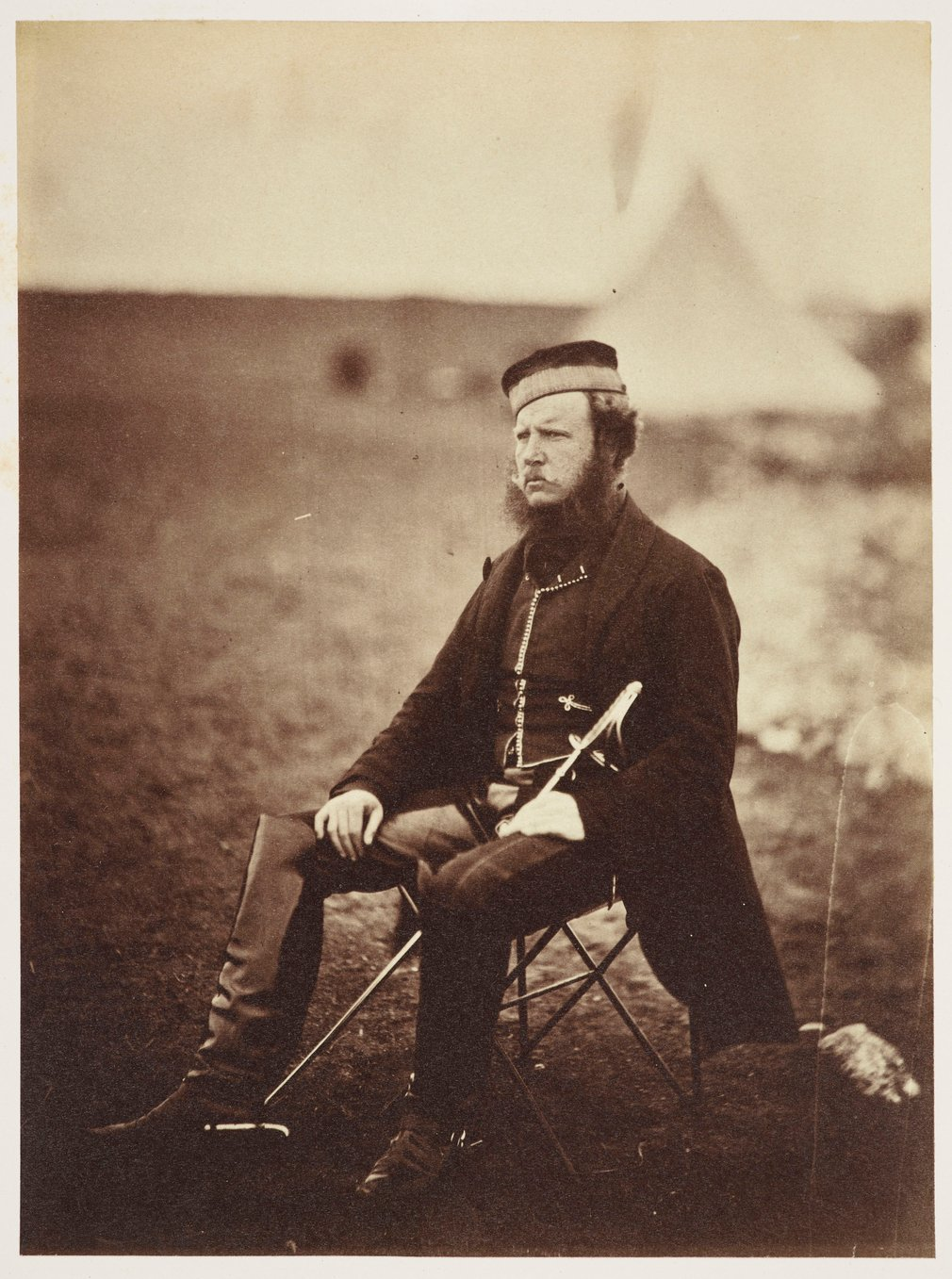 Photograph of Colonel Adye seated in a campsite facing partly left. He is wearing military uniform and has a long sword resting between his legs.Colonel Adye served during the Crimean War and later became the Governor of Gibraltar, where he became known a