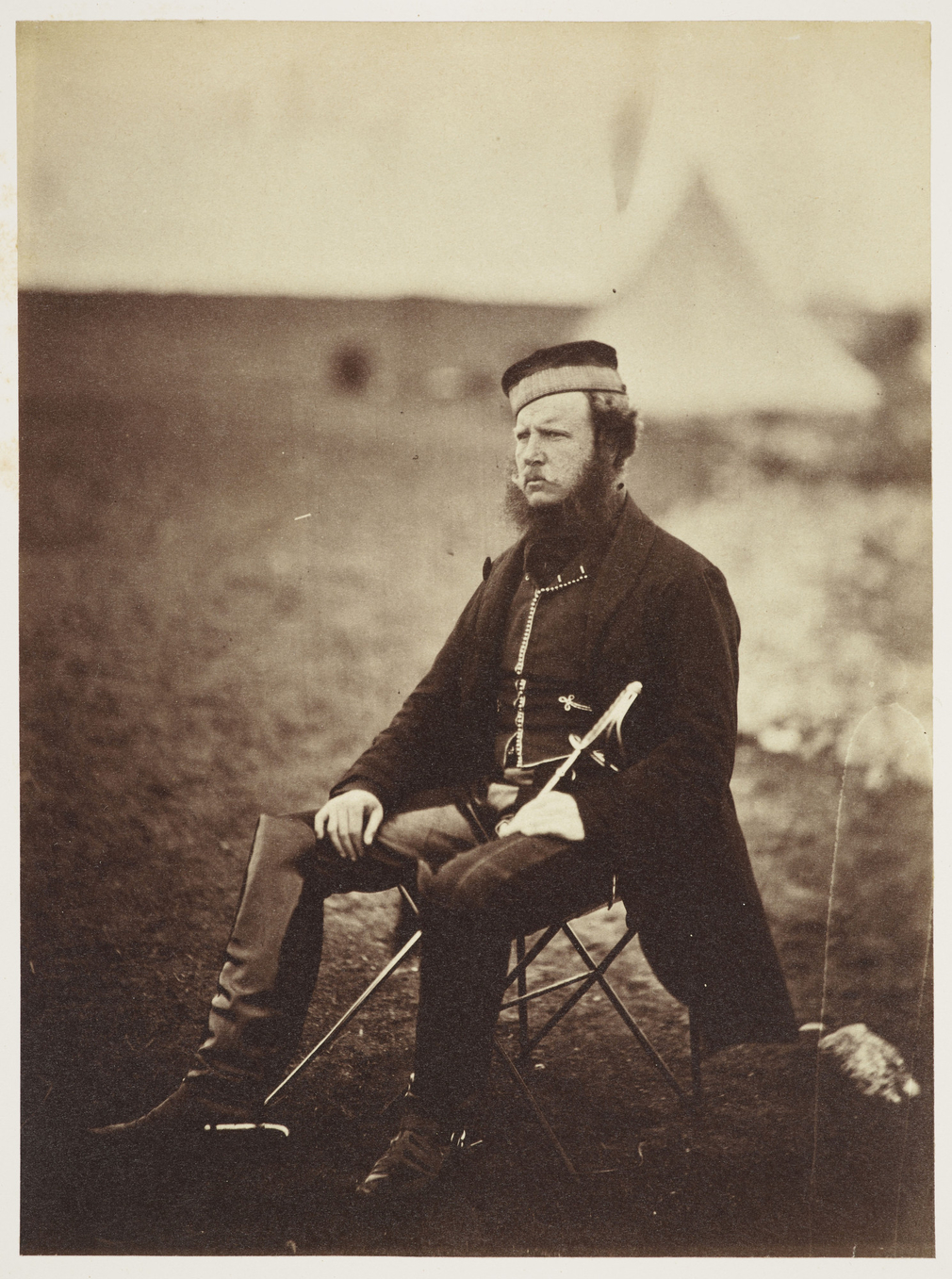 Photograph of Colonel Adye seated in a campsite facing partly left. He is wearing military uniform and has a long sword resting between his legs.<br /><br />Colonel Adye served during the Crimean War and later became the Governor of Gibraltar, where he be