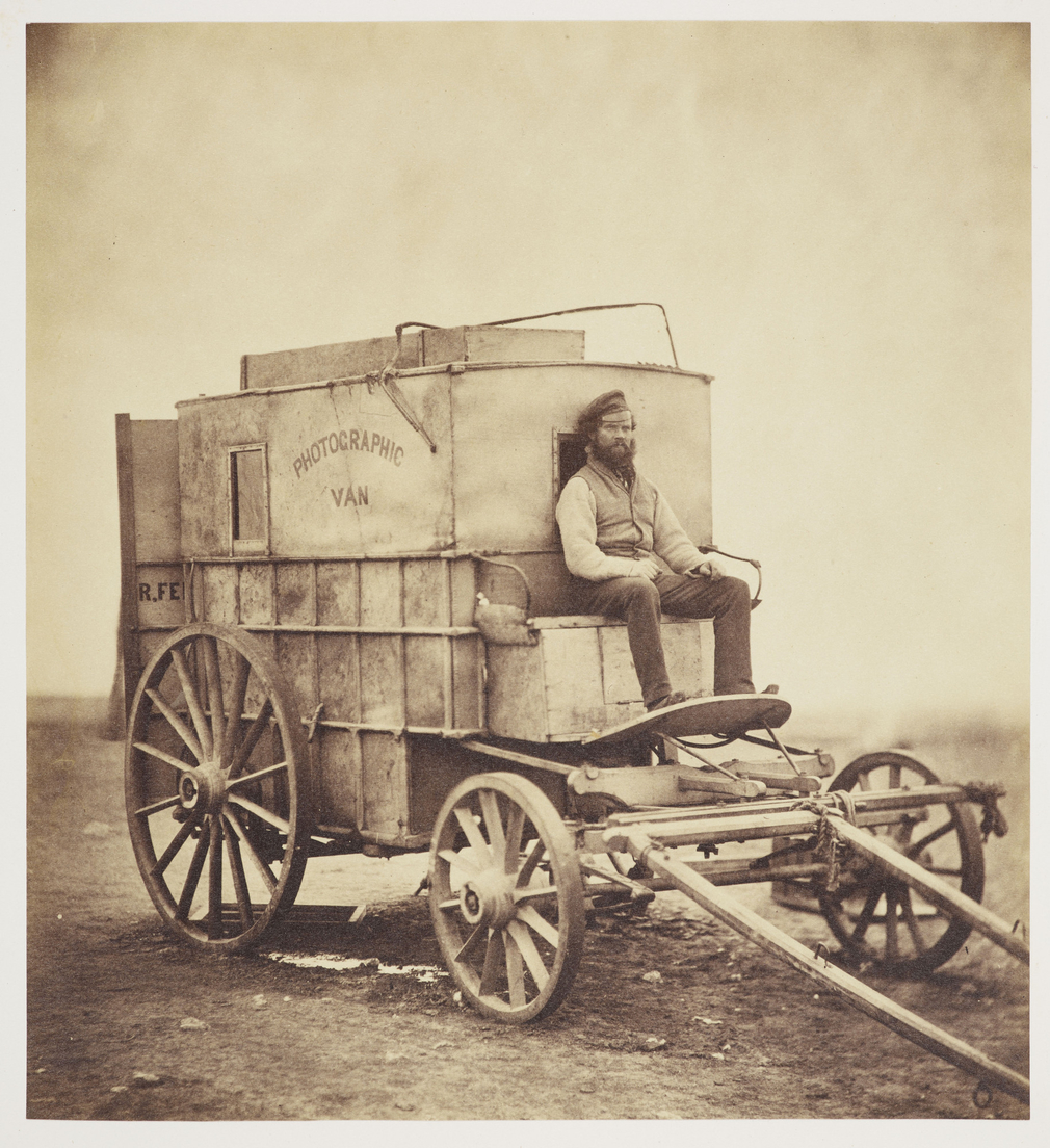 Photograph of Roger Fenton's horse-drawn photographic van, with his assistant Marcus Sparling seated at the front. The van is facing partly right and has 'PHOTOGRAPHIC VAN' printed on the side. 