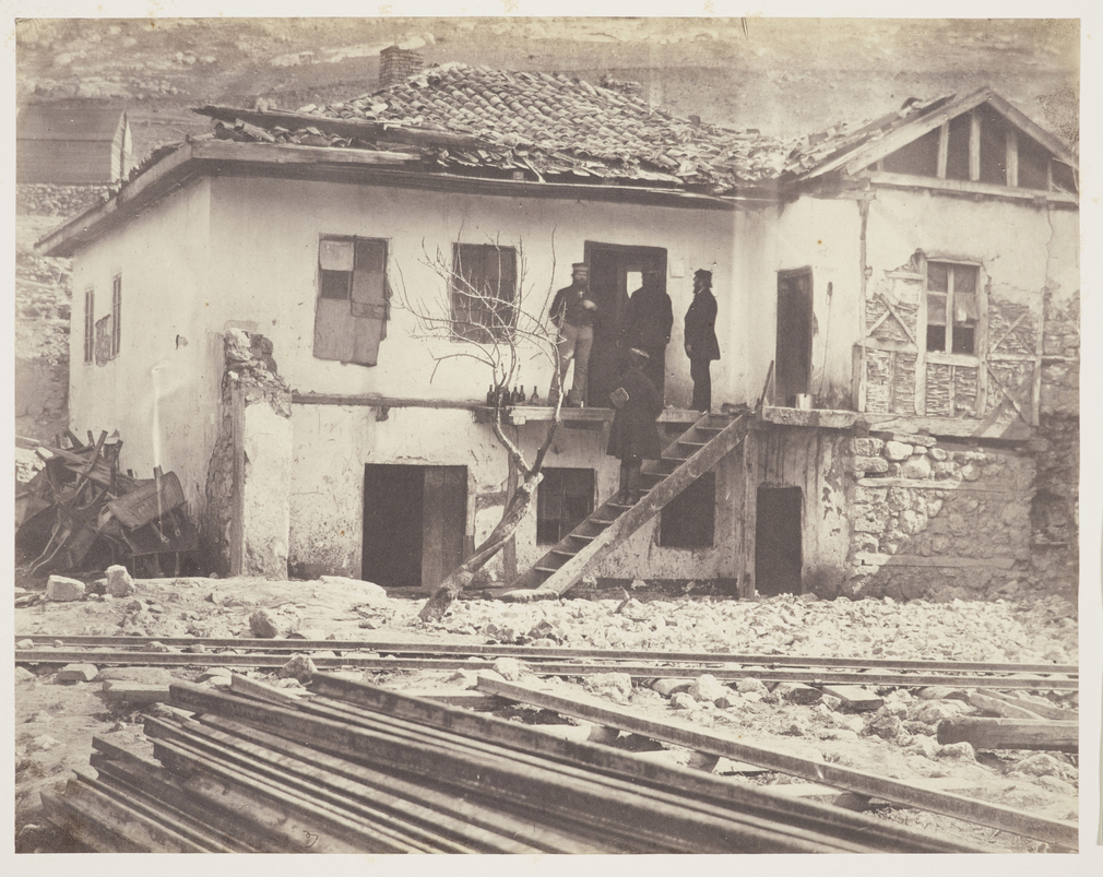 Photograph of the Old Post Office at Balaklava. The building is in poor condition with a damaged tile roof. Four men stand on a wooden platform and staircase at the front of the building, with a row of glass bottles beside them. In the foreground there is