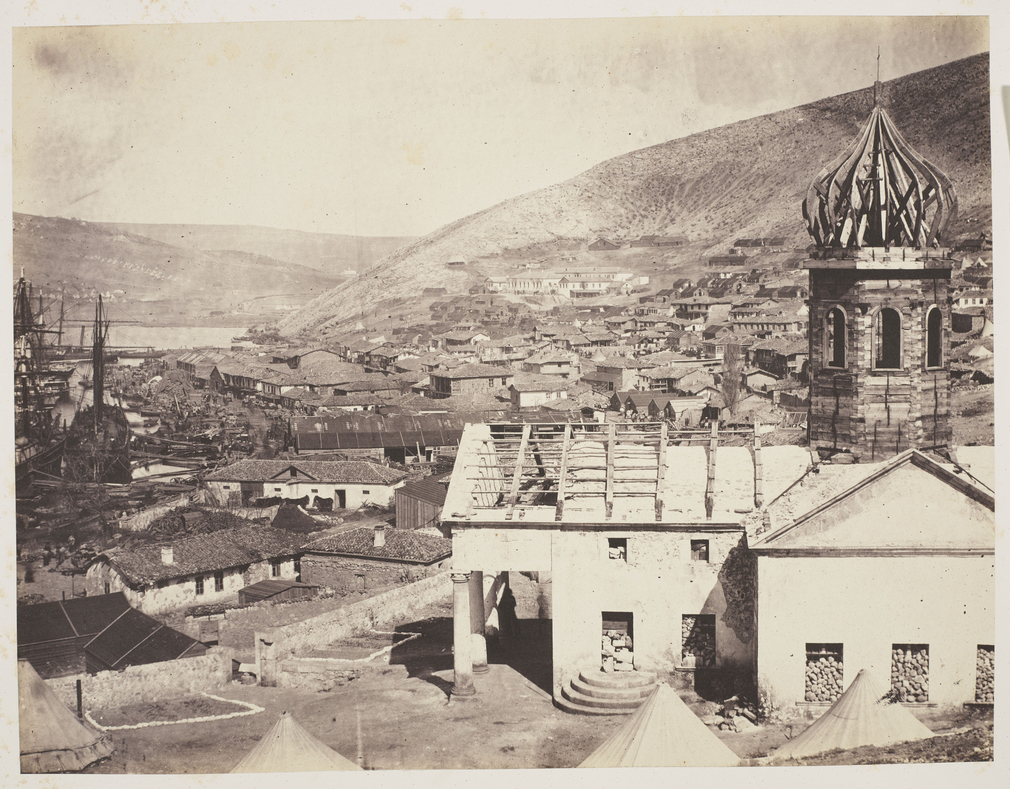 Photograph of Balaklava taken from the Russian Church, showing the upper harbour and the Church of Kadikoi in the distance. The Russian Church is in the foreground to the right. The timber dome and roof are exposed and the doors and windows are filled wit