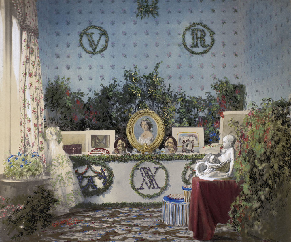Hand coloured photograph of a table with an arrangement of birthday gifts on it, including a framed portrait. There is a 'VA' monogram in the centre of the table, facing outwards. The photograph was taken at Osborne House.