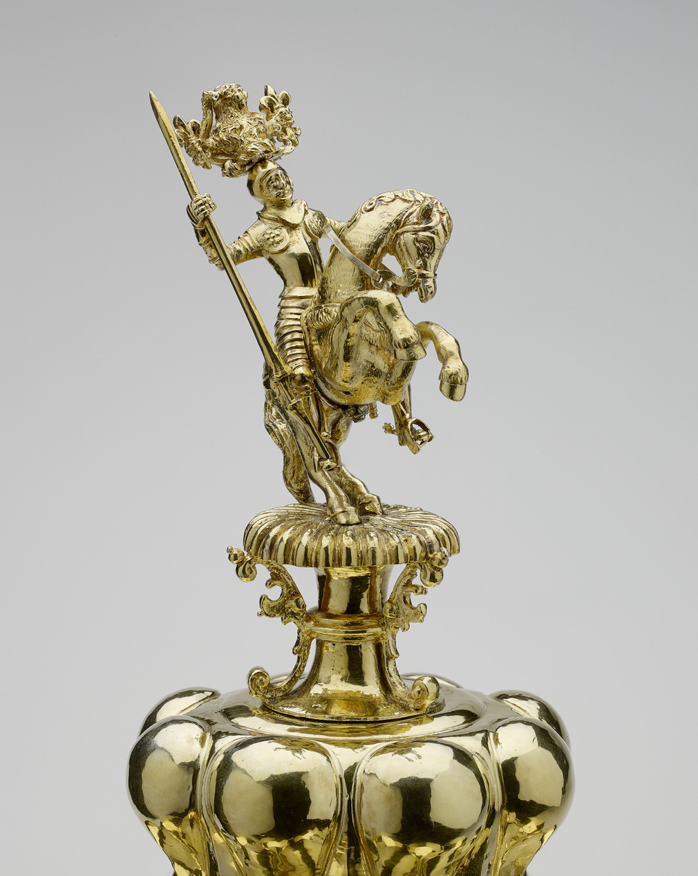 <p>The cup has a high lobed foot mounted with small cast animals &ndash; lizards, snails, a tortoise, a beetle, and a scorpion &ndash; among plants and shells. The stem is formed from the figure of Mucius Scaevola, carrying a gadrooned shield on his left